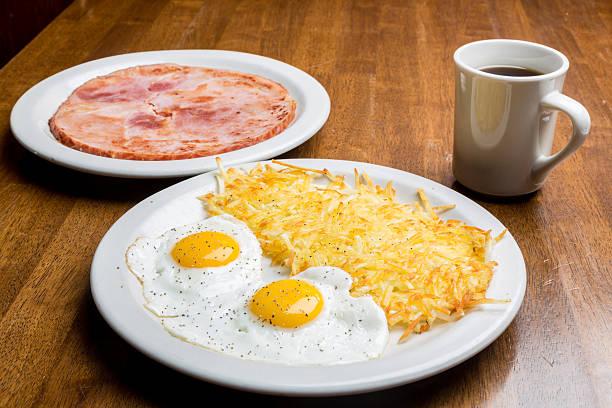 über leicht gebratenem ei, schinken, kaffee und rösti - haschee stock-fotos und bilder