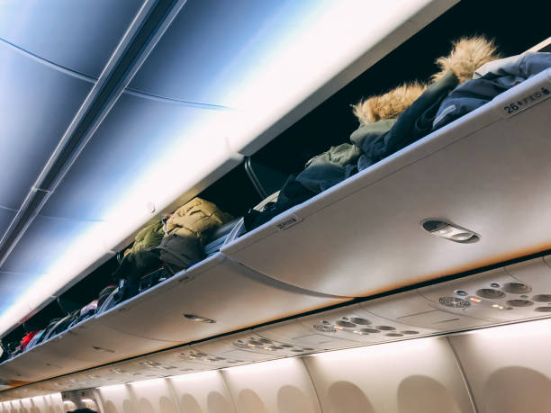 Over head luggage compartment in the airplane stock photo