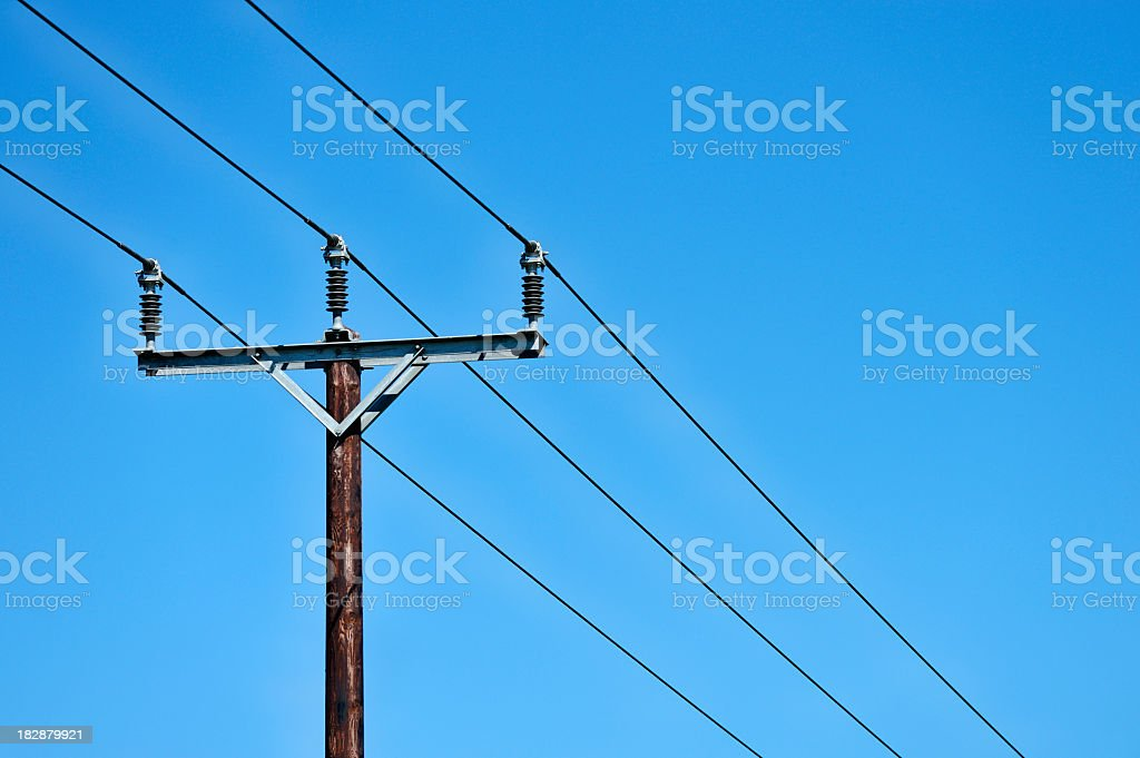 Over head power lines photographed against a clear blue sky. stock photo