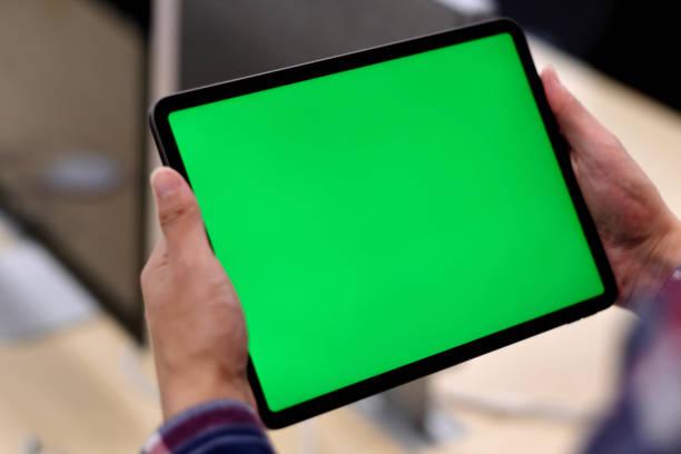 over de schouder van een man met groene scherm tablet pc in office. - green screen stockfoto's en -beelden