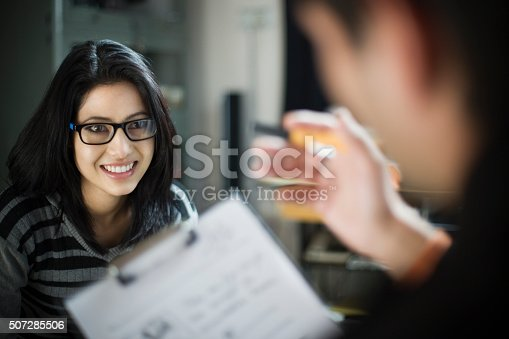 Indoor over shoulder view of a happy, Asian young businesswoman listening to her coworker who is explaining something by holding pen and clipboard to her. Two people, horizontal composition and selective focus.