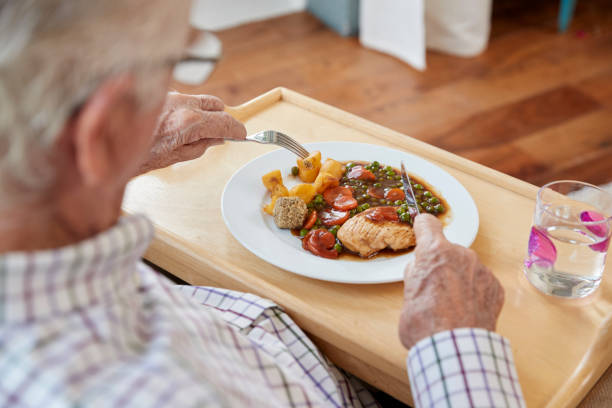 Over shoulder view of senior man eating dinner at home stock photo