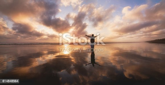 istock Over Stretched man looking towards sunset at Muriwai Beach. 614848564