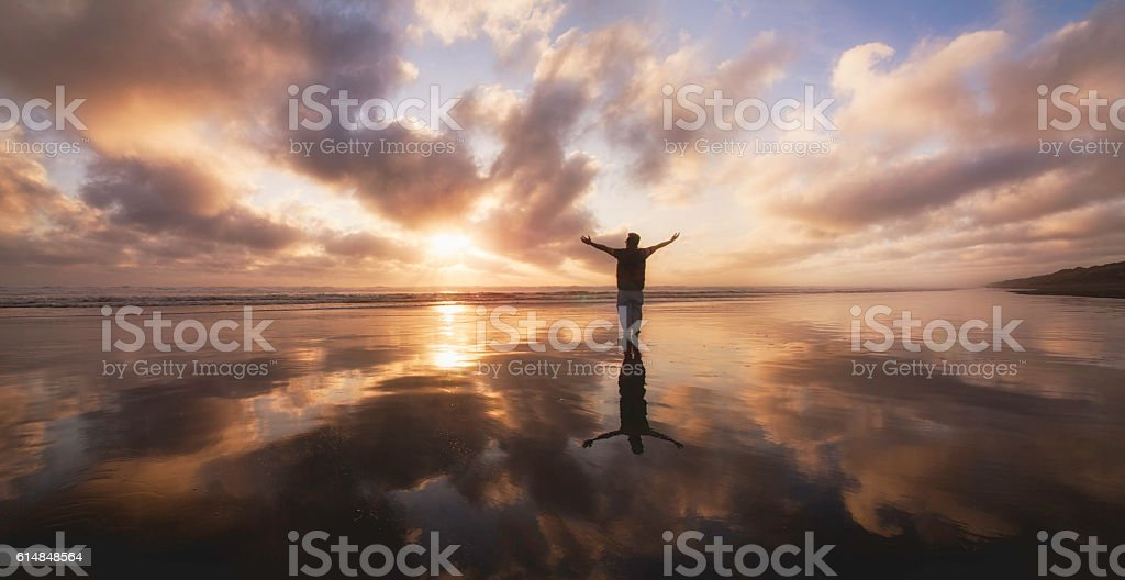 Over Stretched man looking towards sunset at Muriwai Beach. stock photo