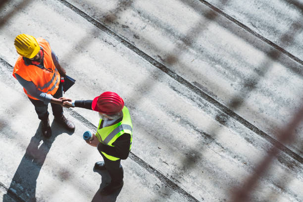 Over the head view of two architects shaking hands on construction site stock photo