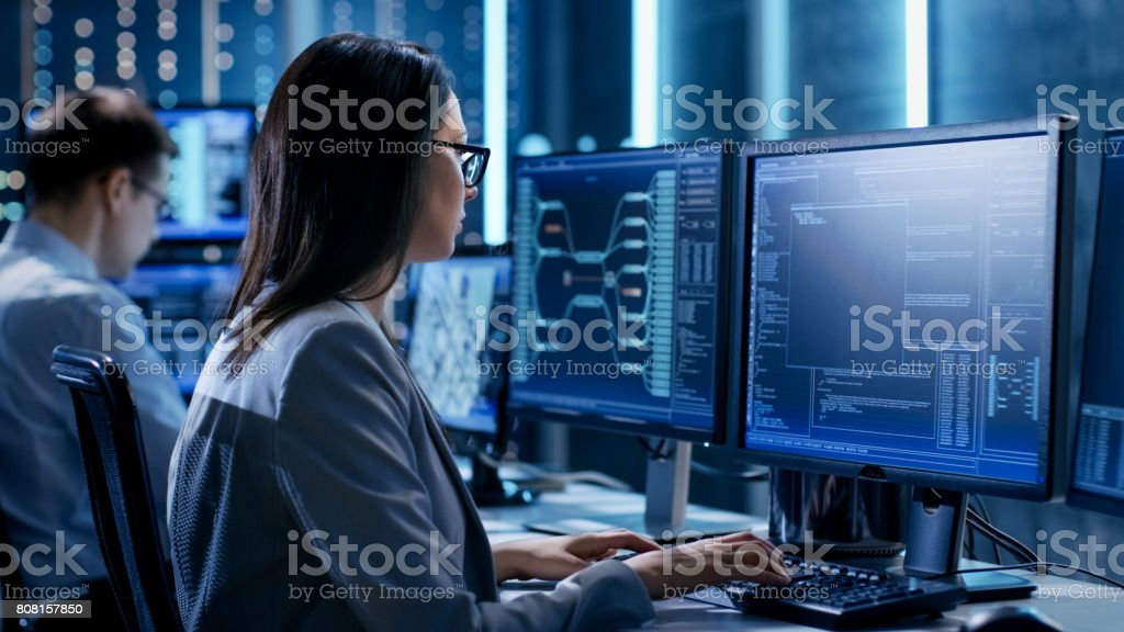 Over The Shoulder Footage of Female IT Engineer Working in Monitoring Room. She Works with Multiple Displays. - Royalty-free Adult Stock Photo