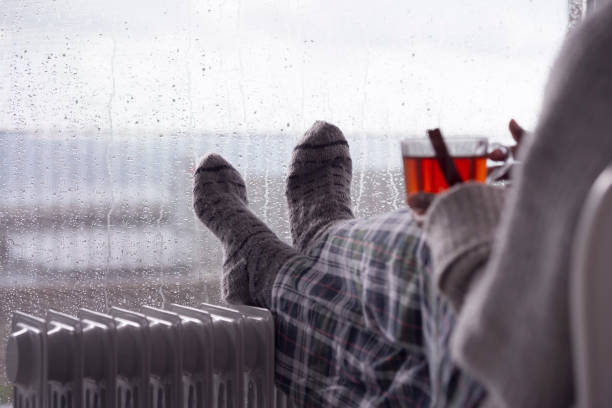Over the shoulder image of a woman drinking tea at home in cold and wet weather. stock photo