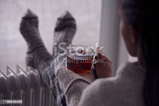 Over the shoulder view of a woman drinking hot tea, heating feet on the radiator heater, wearing woolen socks, sitting next to a window, staying at home in the rainy winter season. Selective focus on the cup of tea.