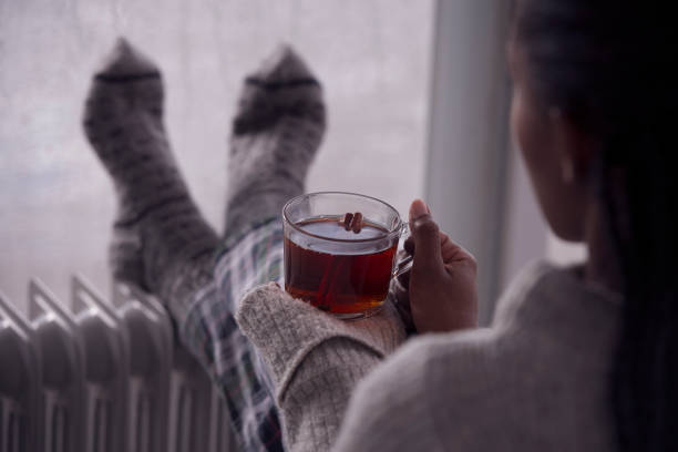 Over the shoulder image of a woman drinking tea at home in cold and wet weather. Over the shoulder view of a woman drinking hot tea, heating feet on the radiator heater, wearing woolen socks, sitting next to a window, staying at home in the rainy winter season. Selective focus on the cup of tea. heat temperature stock pictures, royalty-free photos & images
