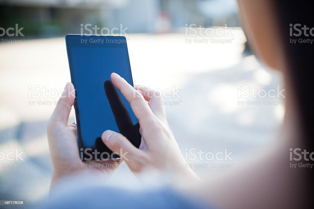 Over the Shoulder of a Woman Using Smart Phone stock photo