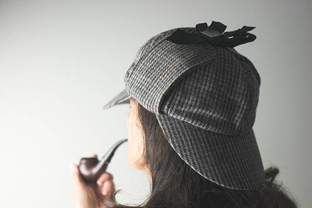 Over the Shoulder Portrait of Woman as Sherlock Holmes A shallow depth of field portrait shot from over the shoulder of a woman wearing a Sherlock Holmes deerstalker hat and holding a smoking pipe.  deerstalker hat stock pictures, royalty-free photos & images