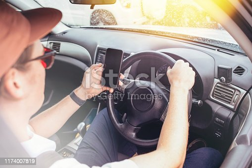 527894422istockphoto Over The Shoulder Shot Of Distracted Driver Talking On Mobile Phone 1174007819