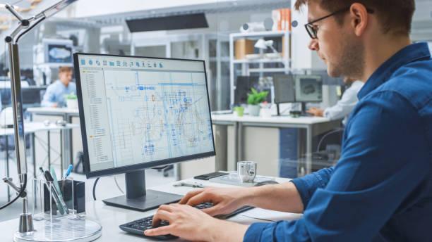 sobre la toma de hombro de ingeniero que trabaja con software cad en computadora de escritorio, la pantalla muestra borradores técnicos y dibujos. en la instalación de ingeniería de fondo especializada en diseño industrial - ingeniero fotografías e imágenes de stock