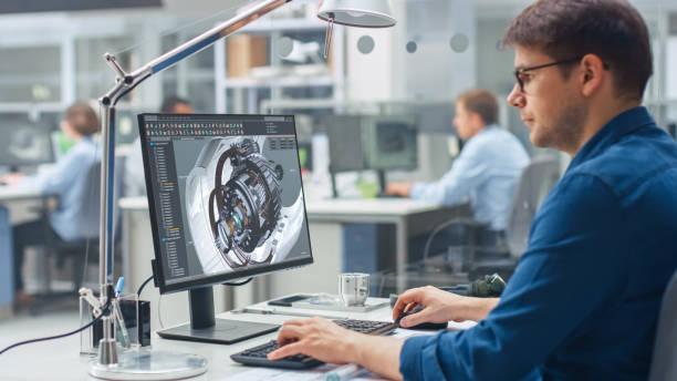 Over the Shoulder Shot des Ingenieurs, der mit CAD-Software auf Desktop-Computern arbeitet, zeigt der Bildschirm technische Details und Zeichnungen. In der Auf die Industrieplanung spezialisierten Einrichtung für Background Engineering – Foto