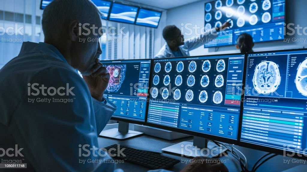 Over the Shoulder Shot of Senior Medical Scientist Working with CT Brain Scan Images on a Personal Computer in Laboratory. Neurologists in Research Center Work on Brain Tumor Cure. stock photo