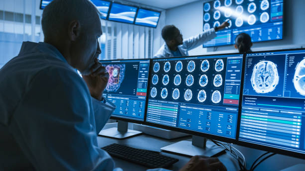 over de schouder schot voor senior medisch wetenschapper werken met ct hersenen scannen afbeeldingen op een personal computer in laboratorium. neurologen in research center werken op brain tumor genezen. - gezondheid stockfoto's en -beelden