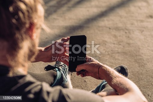 Close up of a blond sportsman using his mobile phone outdoors.