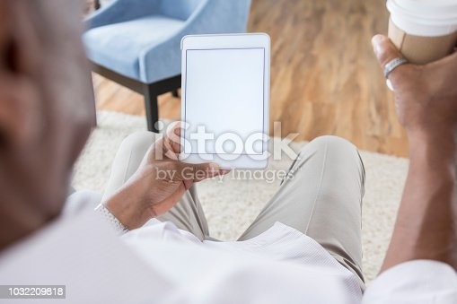 In this over the shoulder view, a man sits in a domestic looking room and holds a cup of coffee in one hand and a digital tablet in the other.  The screen is blank.