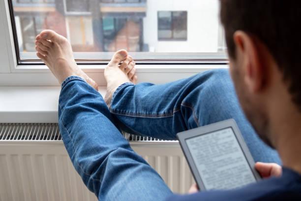 Au-dessus de la vue d'épaule de l'homme de détente dans un jean bleu affichant un livre électronique sur l'appareil numérique par la fenêtre. Concentrez-vous sur les pieds nus se trouvant sur un rebord de fenêtre dans un appartement moderne lum - Photo