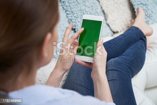 Over The Shoulder View Of Woman Lying On Sofa Using Green Screen Mobile Phone At Home
