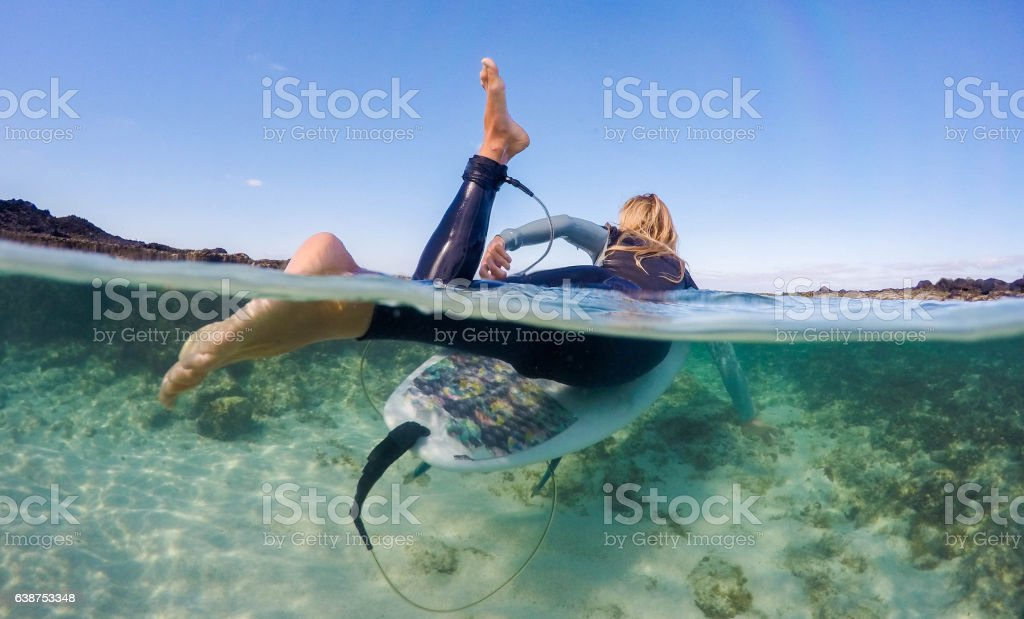 Over under photoof women paddling out on a surfboard stock photo