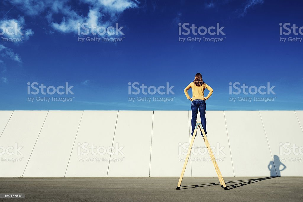 Overcome adversity Woman on top of folding ladder looks across a wall. 30-39 Years Stock Photo