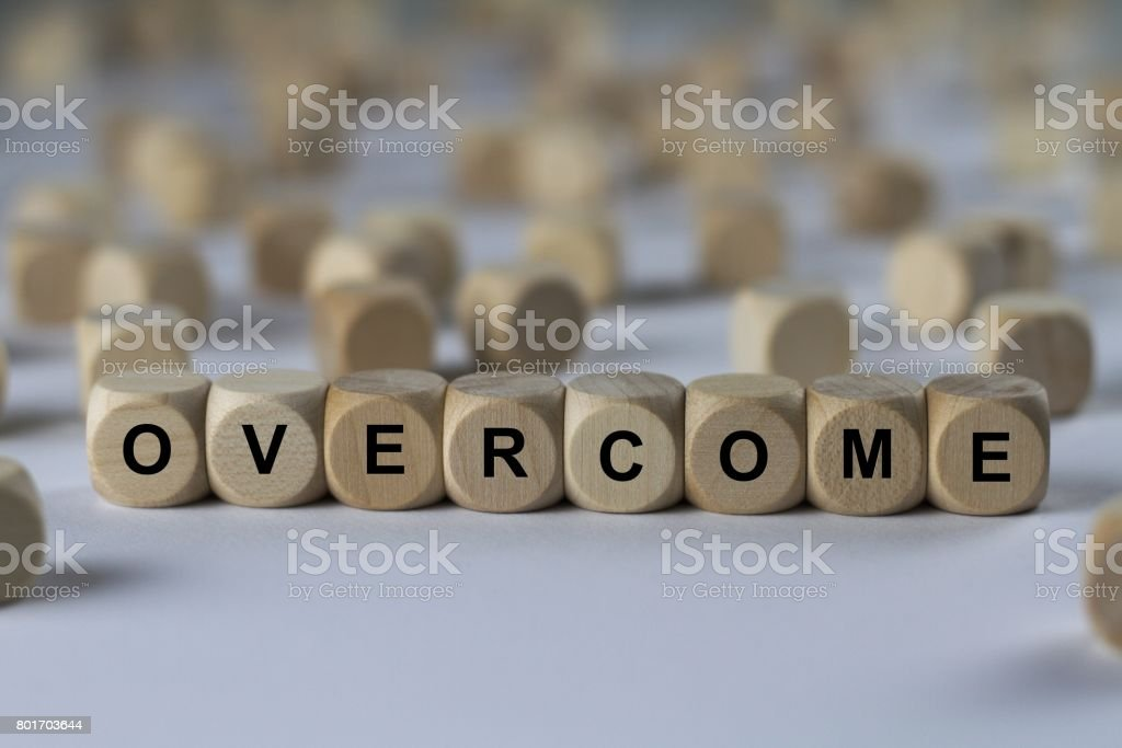 overcome - cube with letters, sign with wooden cubes stock photo