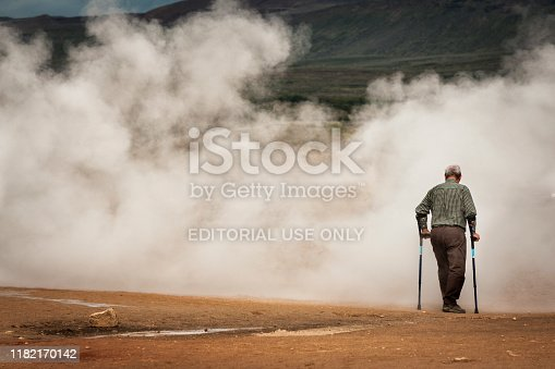Mytvan, Iceland - August 29, 2010: A senior man leaning on two braced canes walks toward steam at a geothermal area in the volcanic landscape, Hverir, Iceland, Europe, USA