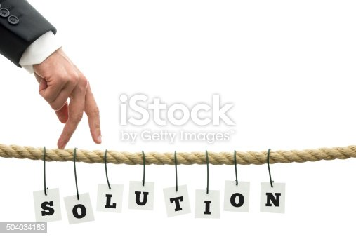 Businessman walking his fingers along a frayed rope wit sign Solution hanging off it. Conceptual of overcoming problems.