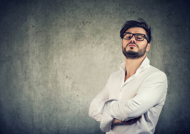 Overconfident stylish man in glasses Young egocentric man in glasses holding hands crossed and looking pompously at camera on gray background arrogant stock pictures, royalty-free photos & images