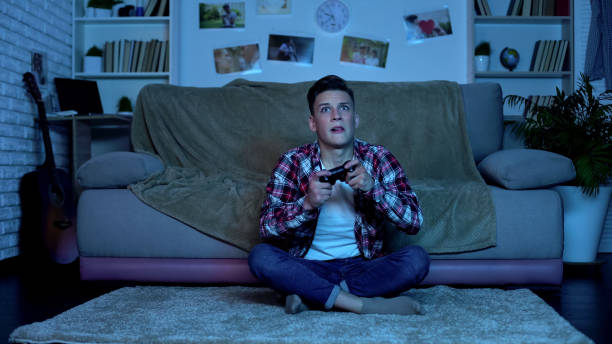 overemotional teenager plating video game, unstable and uncontrolled emotions - divano procrastinazione foto e immagini stock