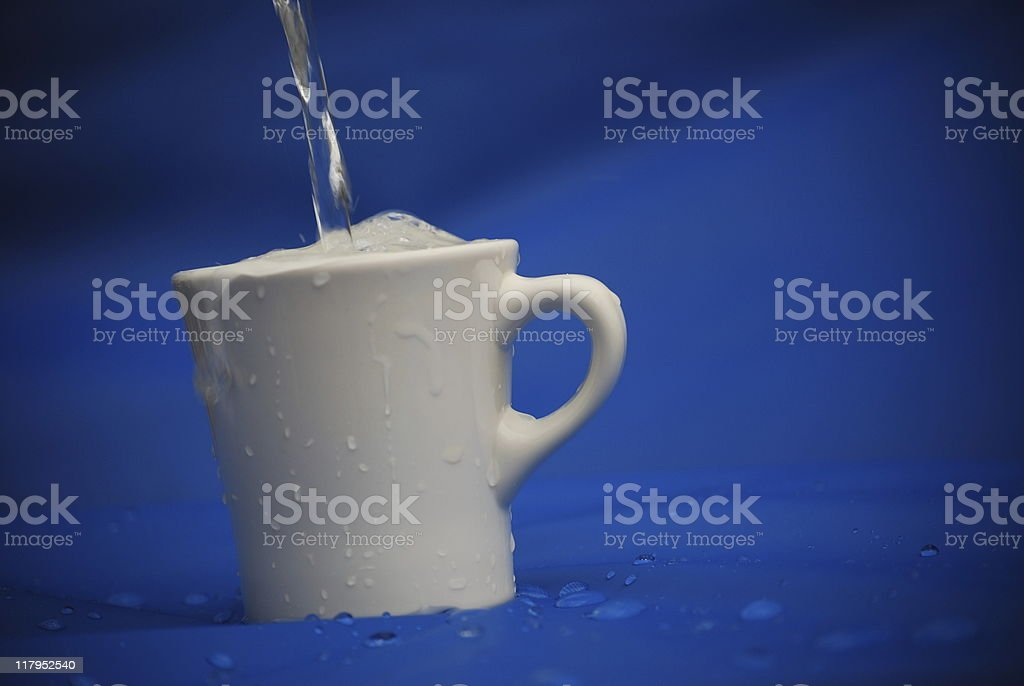 overflowing cup of water royalty-free stock photo