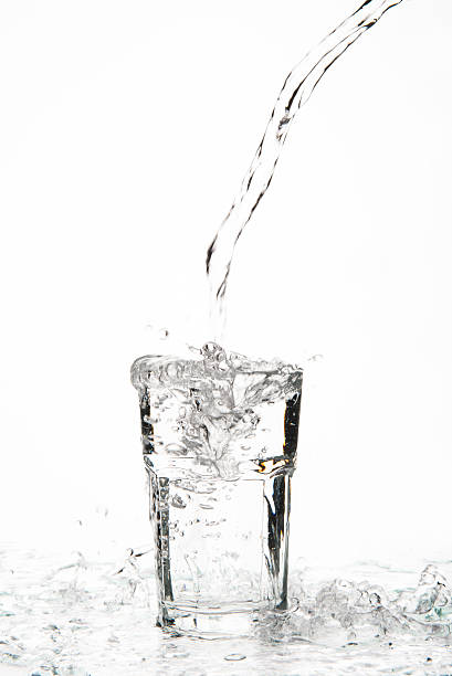 overflowing glass of water on a glass table - overflowing stock photos and pictures