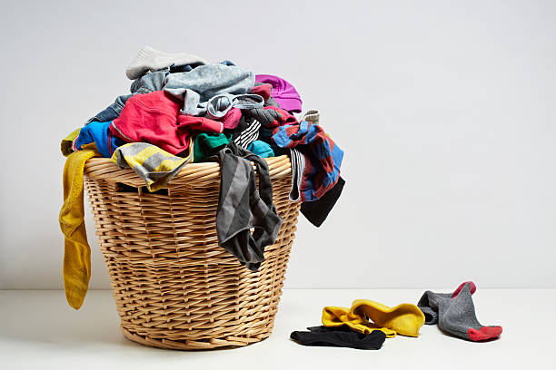overflowing laundry basket - overflowing stock photos and pictures