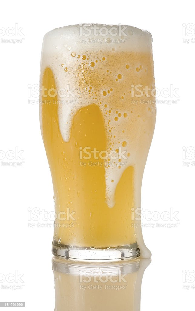 Overflowing pint of beer on a white background stock photo