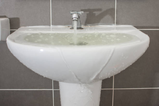 Overflowing water from the washbasin stock photo