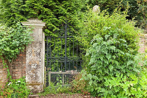 überwachsen schwarzem schmiedeeisen gates. - steine für gartenmauer stock-fotos und bilder