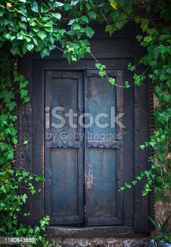 Ivy Surrounding An Old Wooden Door To A Secret Garden At An Old Mansion House