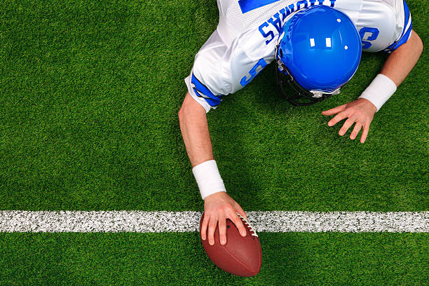 Overhead American football player one handed touchdown Overhead photo of an American football player making a one handed touchdown. The uniform he's wearing is one I had made using my name and does not represent any actual team colours. american football uniform stock pictures, royalty-free photos & images
