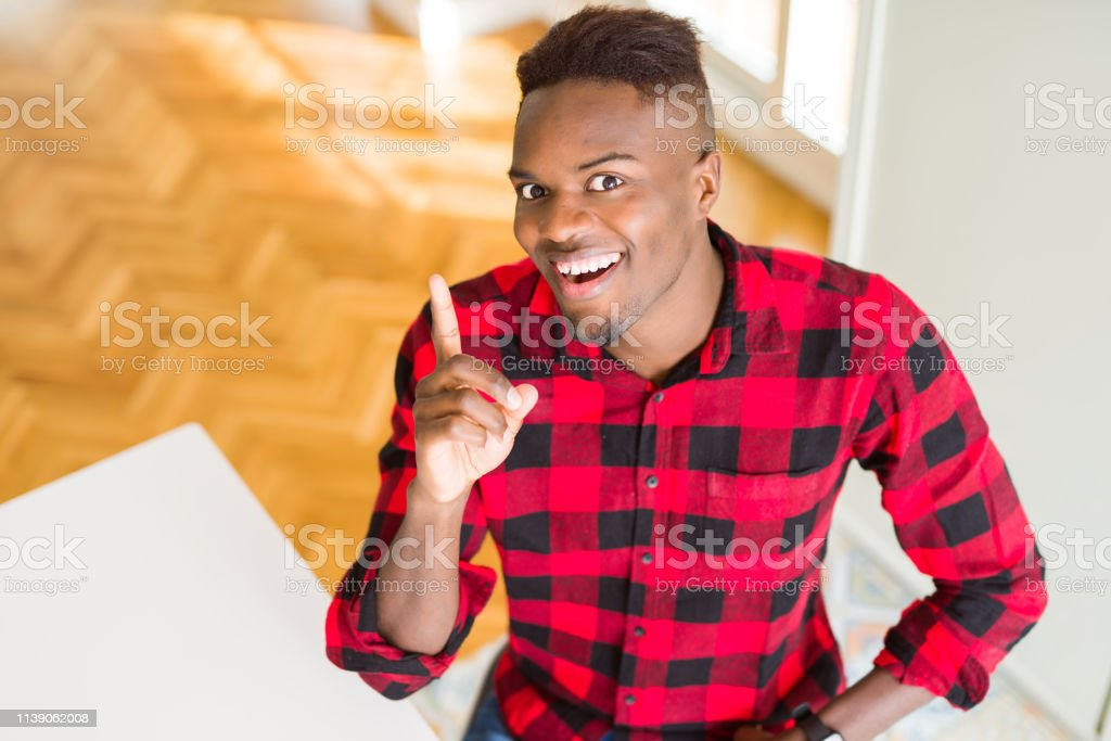 Overhead angle of handsome african american man pointing finger up with successful idea. Exited and happy. Number one. – zdjęcie