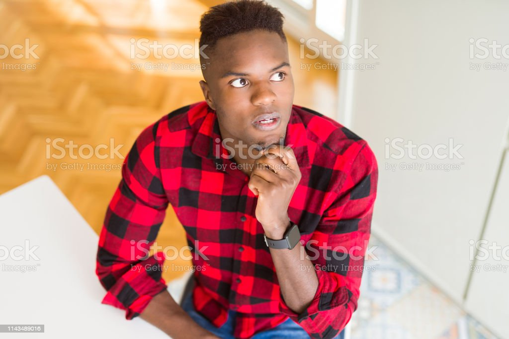 Overhead angle of handsome african american man with hand on chin thinking about question, pensive expression. Smiling with thoughtful face. Doubt concept. – zdjęcie