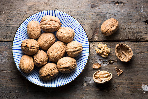 overhead bowl of walnuts on a rough wooden background - walnut stock photos and pictures