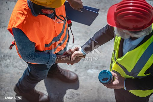 istock Overhead Close-up of Construction Coworkers Shaking Hands 1185046270