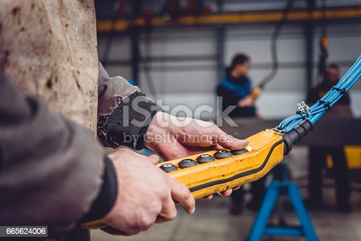 Overhead Crane Operator in big industrial hall