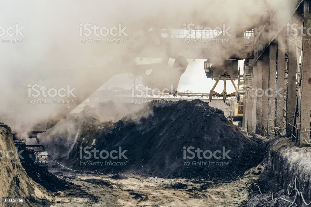 Overhead crane with mechanical multivalve clamshell grab and bucket excavator in the dusty of industrial site. Heavy industry background. stock photo