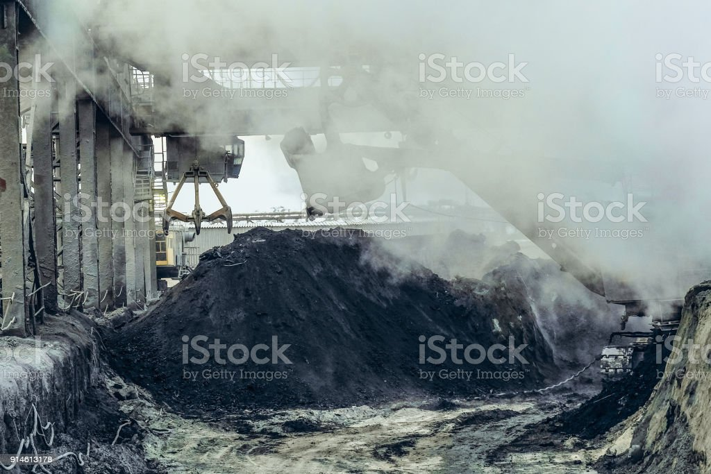 Overhead crane with mechanical multivalve clamshell grab and bucket excavator in the hot dusty of industrial site. Heavy industry background. stock photo