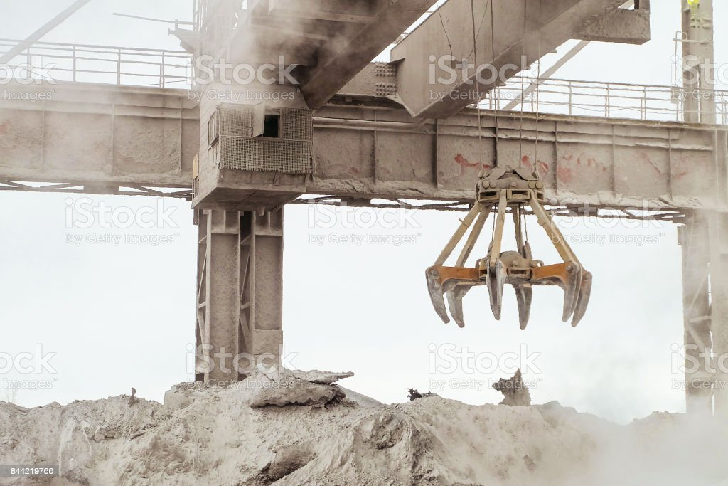 Overhead crane with mechanical multivalve clamshell grab in hot outdoors industrial plant shop. Heavy industry. stock photo