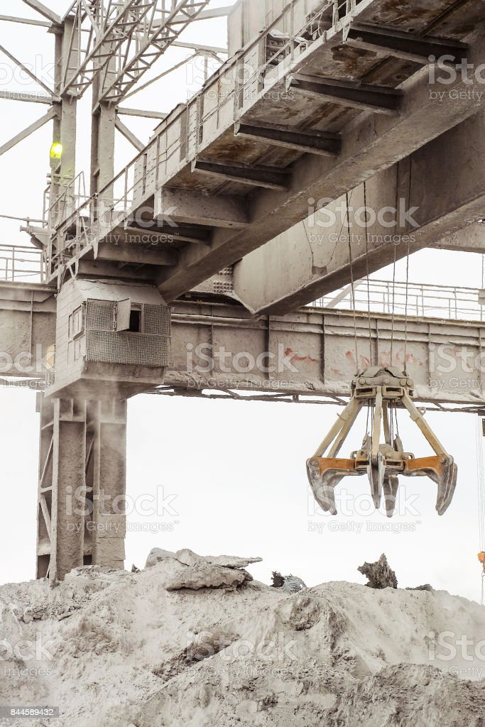Overhead crane with mechanical multivalve clamshell grab in outdoors industrial plant shop. Heavy industry. stock photo