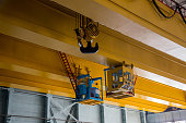 Overhead crane with vacuum handling grippers is lifting iron sheet.