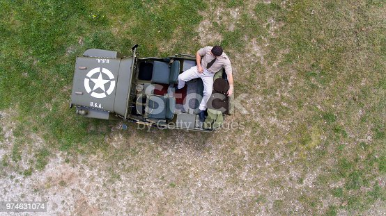 From above view of world war 2 army, military officer sitting on the back truck, of army vehicle by drone